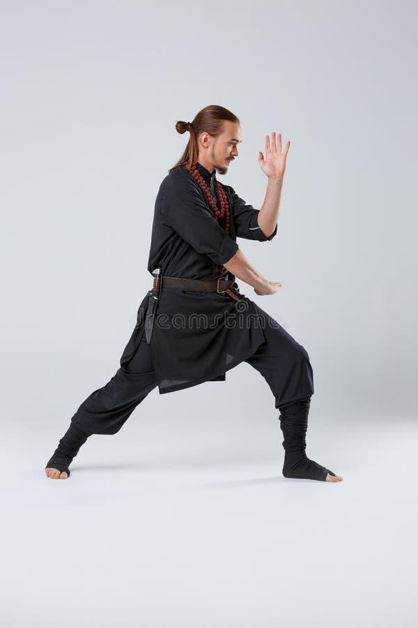 Un hombre del ninja se lanza adelante y se protege contra el fondo gris Primer de la vista lateral fotografía de archivo