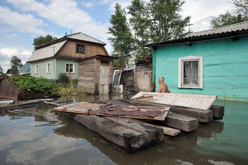 Un hombre desconocido en un diagrama inundado cerca de su casa imágenes de archivo libres de regalías