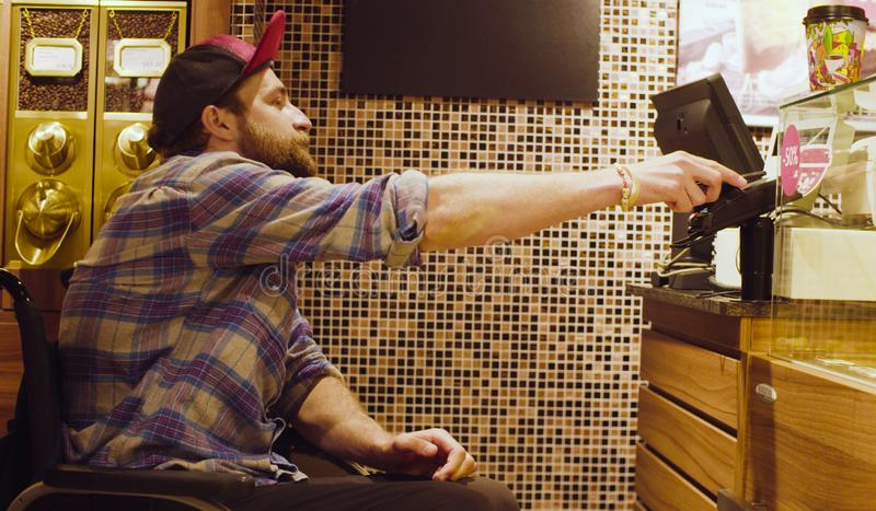 Un hombre discapacitado en una silla de ruedas en el café imágenes de archivo libres de regalías