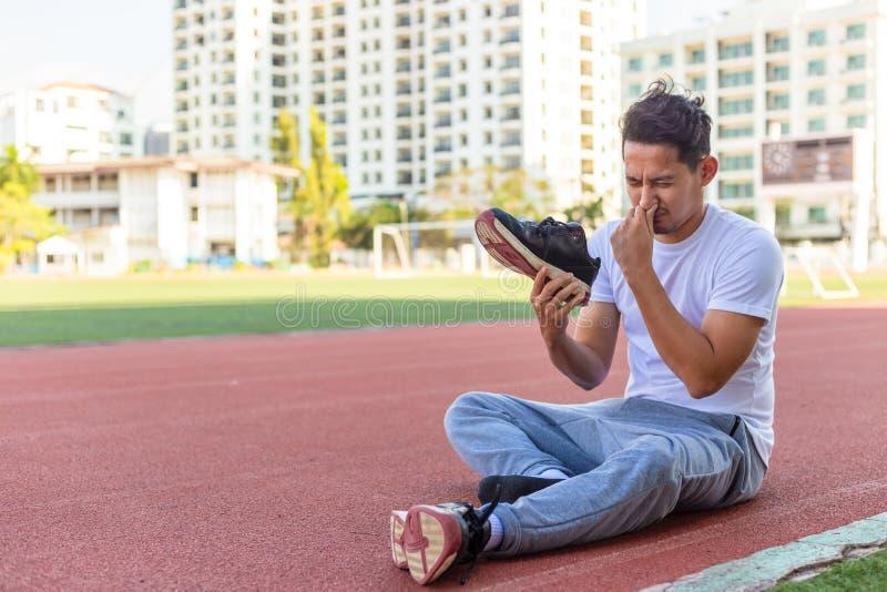 Un hombre disgustado por el olor de su zapato de correr. Un hombre deportivo sentado en la carrera de la pista en el estadio foto de archivo