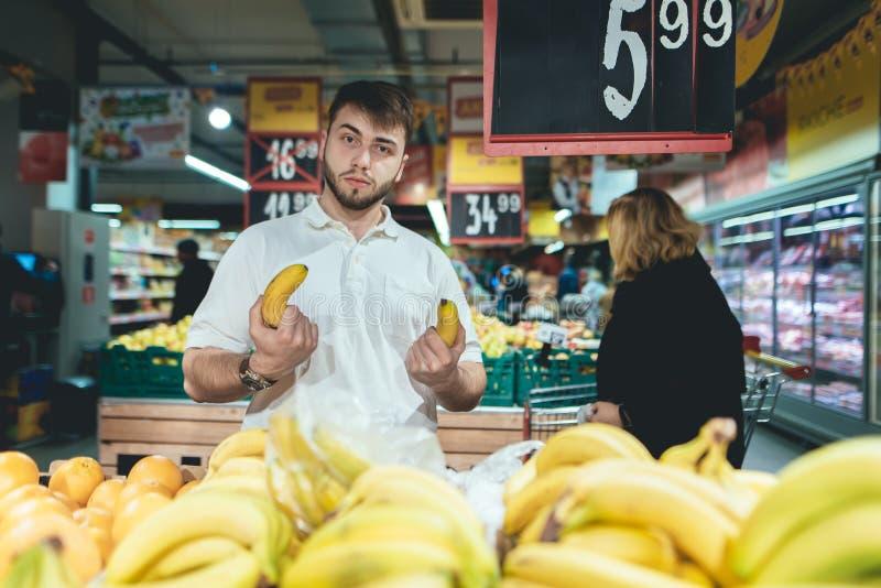 Un hombre divertido sostiene plátanos en sus manos mientras que hace compras en un supermercado El plátano es como una pistola fotos de archivo libres de regalías