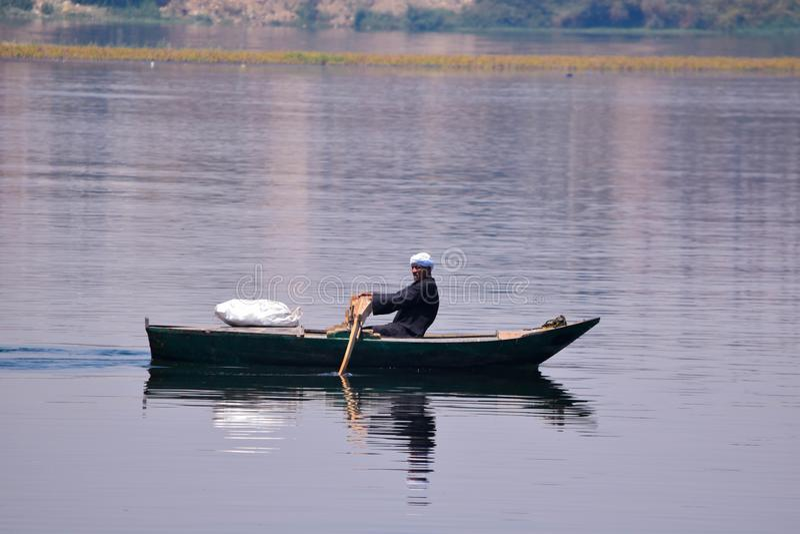 Un hombre egipcio que rema un barco en el Nilo foto de archivo libre de regalías