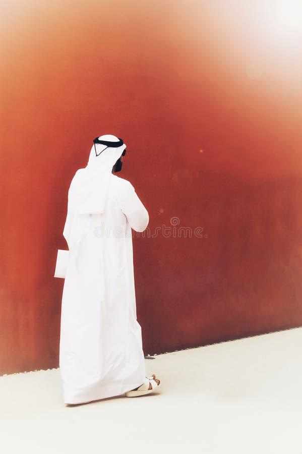 Un hombre elegante con las gafas de sol y los vestidos árabes que camina en las calles de su país Concepto árabe de la pertenenci foto de archivo