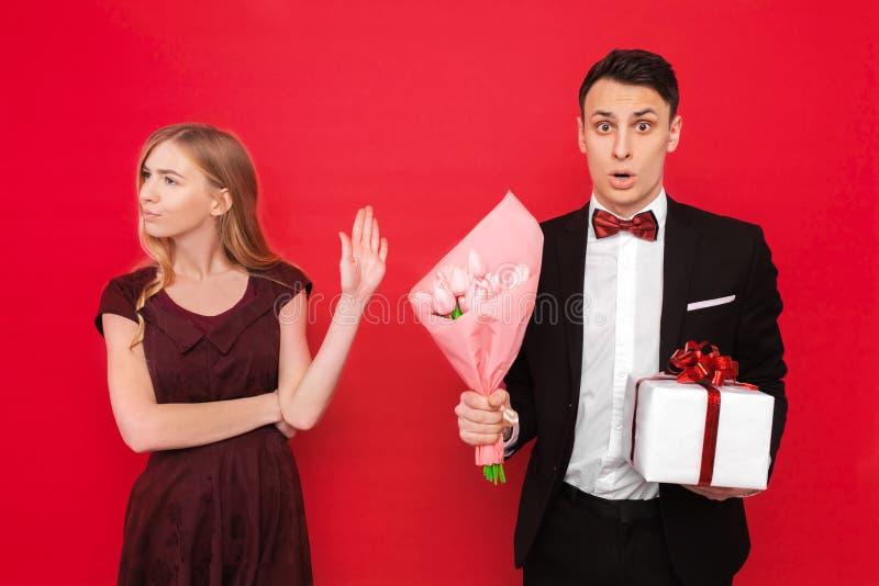 Un hombre elegante, da un regalo y un ramo de flores, mujer descontentada que no quiera aceptar un regalo, en un fondo rojo fotos de archivo