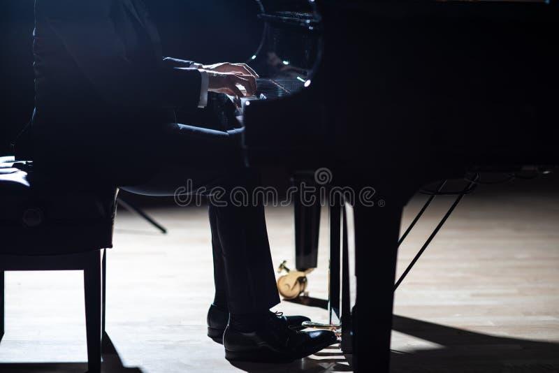 Un hombre elegante en un traje negro que juega el piano de cola en la etapa en una sala de conciertos, cierre para arriba, irreco fotografía de archivo