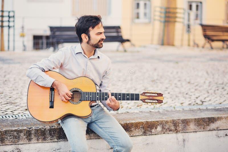 Un hombre elegante lindo con una barba se sienta en un encintado concreto en la calle y toca una guitarra acústica y sonríe El mú fotografía de archivo libre de regalías