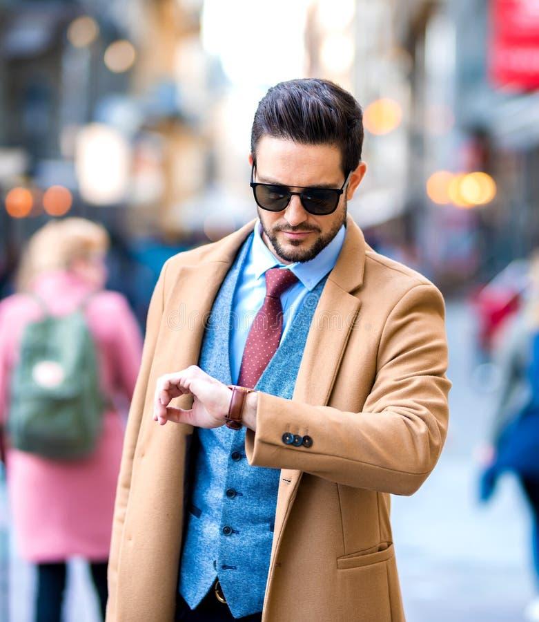 Un hombre elegante que camina en las calles y que comprueba el tiempo imagen de archivo