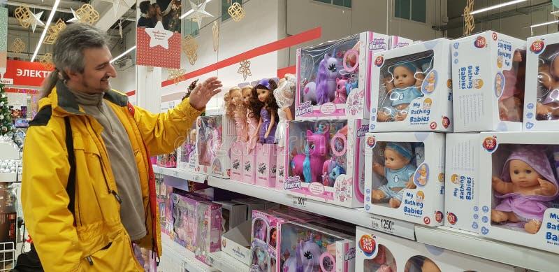 Un hombre elige los regalos para los niños en el departamento de los juguetes, muñecas en el supermercado foto de archivo
