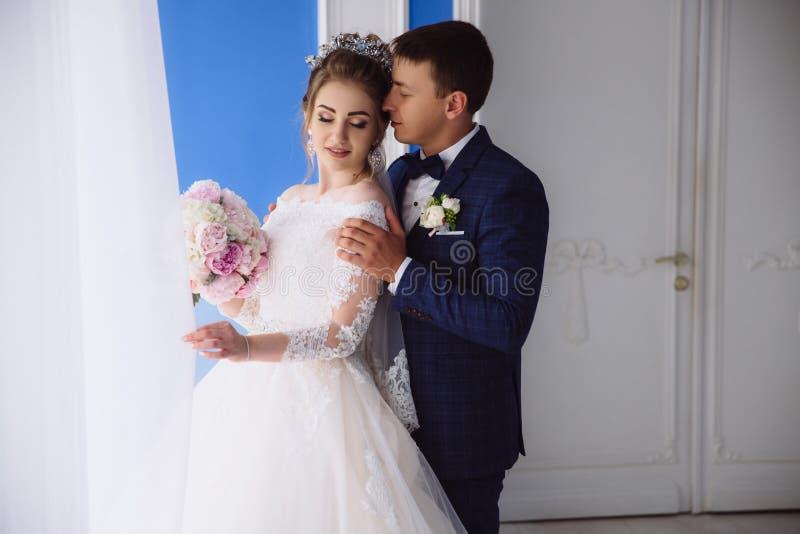 Un hombre en amor en un vestido de boda saca a su novia e inhala el olor de su pelo El par en amor está tomando el sol adentro foto de archivo