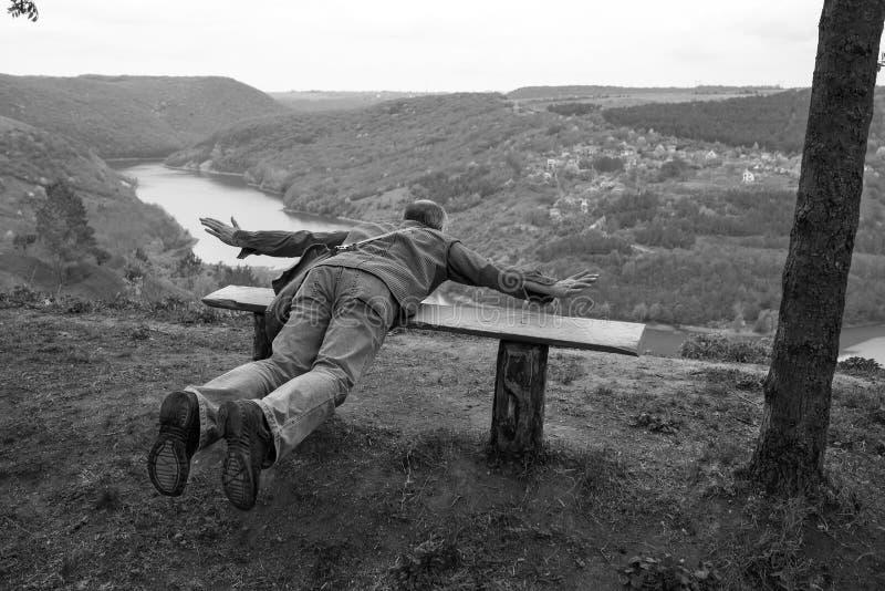 Un hombre en un banco en un acantilado imagen de archivo
