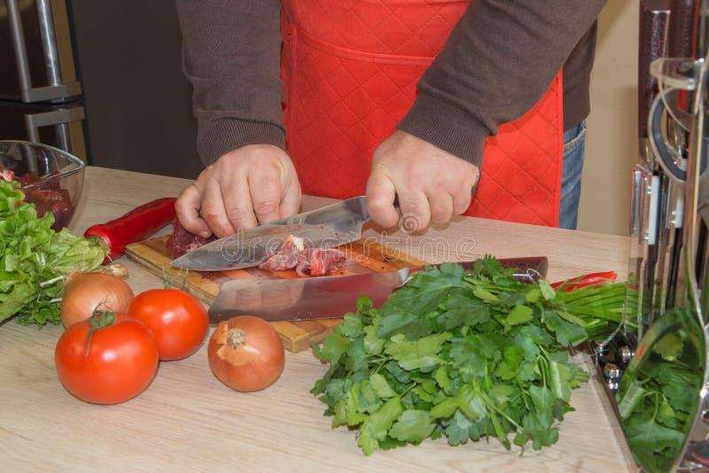 Un hombre en un delantal de la cocina, carne en un tablero y una tabla de madera foto de archivo