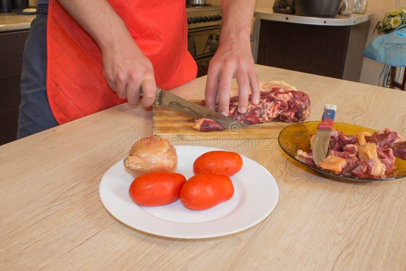 Un hombre en un delantal de la cocina, carne en un tablero y una tabla de madera fotos de archivo libres de regalías