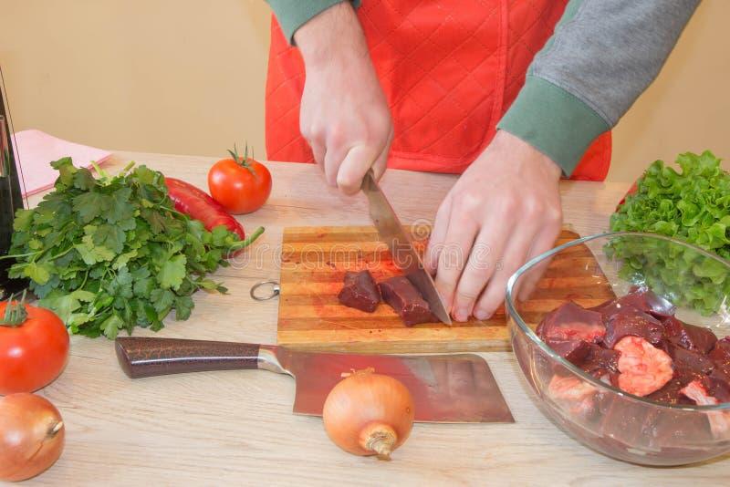 Un hombre en un delantal de la cocina, carne en un tablero y una tabla de madera, un cuchillo y verduras fotos de archivo libres de regalías