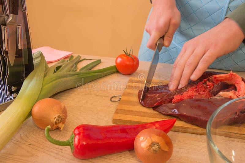 Un hombre en un delantal de la cocina, carne en un tablero y una tabla de madera, un cuchillo y verduras fotos de archivo