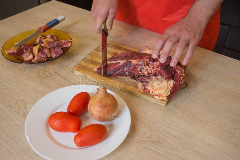 Un hombre en un delantal de la cocina, carne en un tablero y una tabla de madera, un cuchillo y verduras imagen de archivo