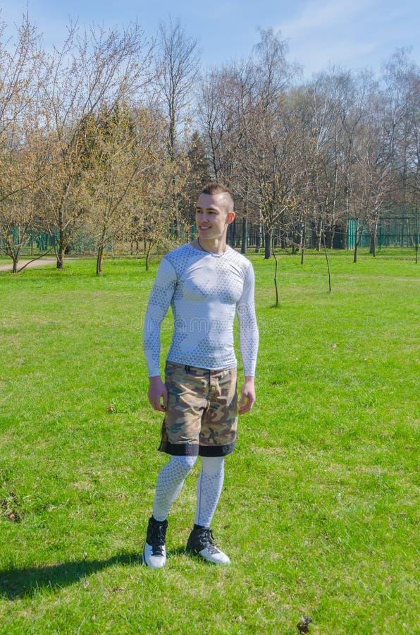 Un hombre en deportes viste en el verano, entrena en el parque fotos de archivo libres de regalías