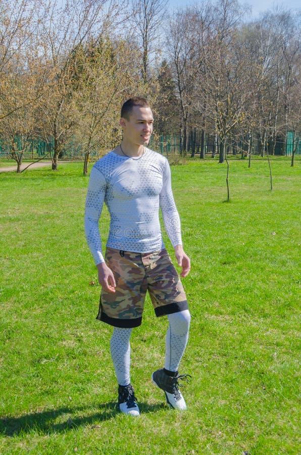 Un hombre en deportes viste en el verano, entrena en el parque imágenes de archivo libres de regalías