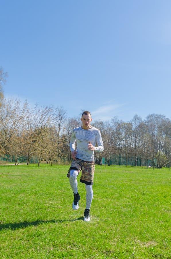 Un hombre en deportes viste en el verano, entrena en el parque foto de archivo libre de regalías
