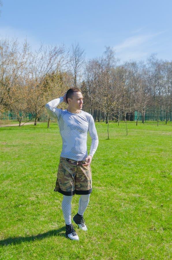 Un hombre en deportes viste en el verano, entrena en el parque fotografía de archivo libre de regalías