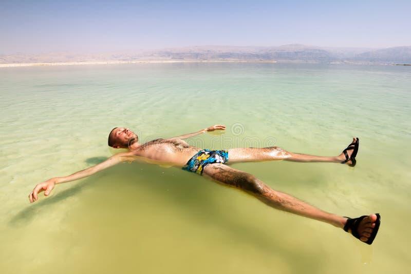 Un hombre en el agua del mar muerto en Israel
