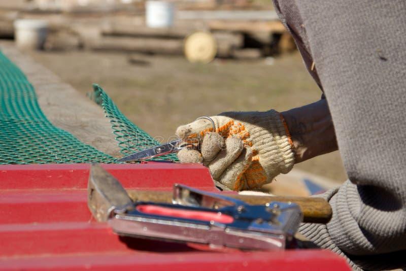 Un hombre en el pueblo está reparando una jaula para un pájaro Constructio imagen de archivo libre de regalías
