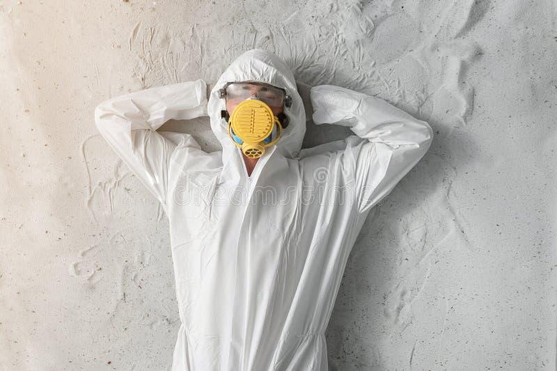Un hombre en el uniforme protector blanco, el respirador y vidrios transparentes plásticos fotos de archivo libres de regalías