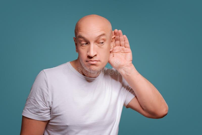 Un hombre en un fondo azul en llevar a cabo sus manos cerca de su oído, escuchando detras de las puertas fotos de archivo libres de regalías