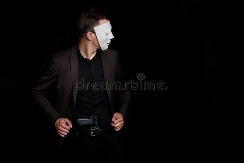 Un hombre en un fondo negro en una máscara blanca Con un arma en sus pantalones fotografía de archivo
