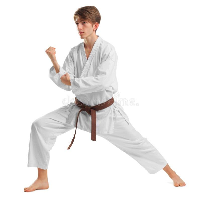 Un hombre en un kimono en una postura que lucha en un fondo blanco aislado foto de archivo