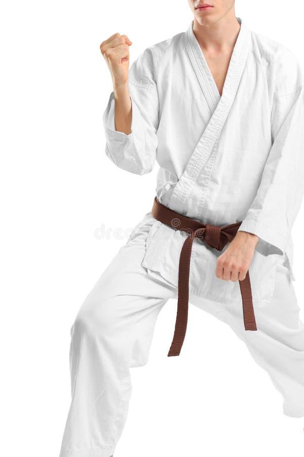 Un hombre en un kimono en una postura que lucha en un fondo blanco aislado imagen de archivo libre de regalías