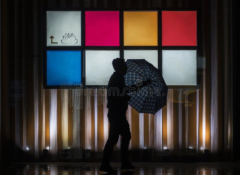 Un hombre en la calle en la noche lluviosa fotografía de archivo