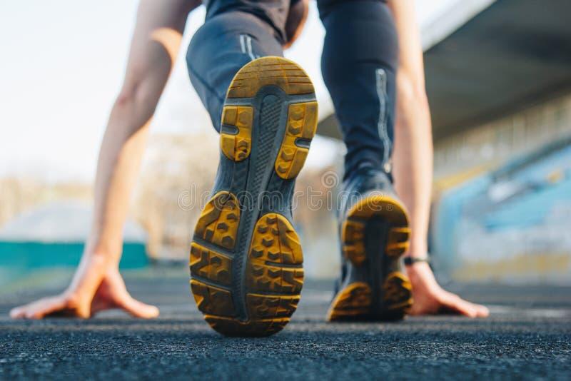 Un hombre en la l?nea del comienzo aguarda el comienzo del sprint estadio, pista de goma Competencias del atletismo Corredor del  fotografía de archivo
