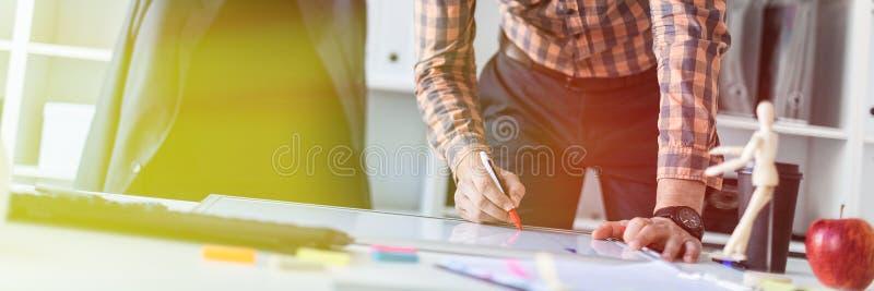 Un hombre en la oficina se está colocando cerca de la tabla y dibuja a un marcador en el tablero magnético imagen de archivo libre de regalías