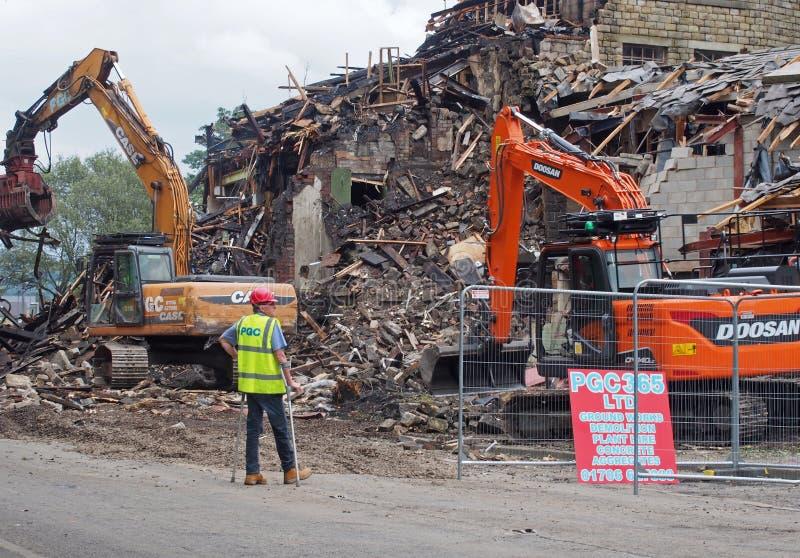 Un hombre en las muletas en maquinaria de construcción protectora de la ropa de trabajo en la demolición del edificio del molino  fotos de archivo