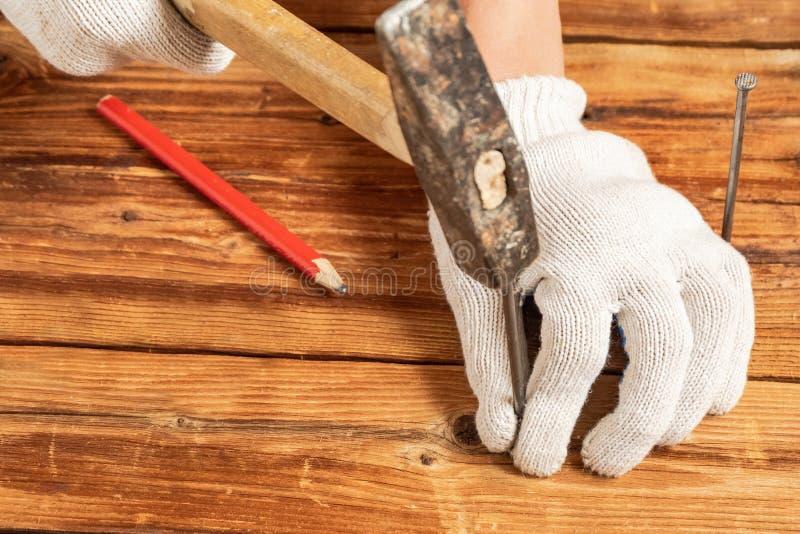 Un hombre en los guantes blancos está martillando un clavo en superficies de madera fotos de archivo