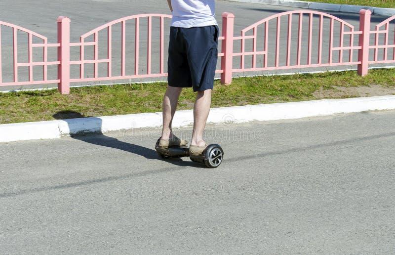 Un hombre en los pantalones cortos que montan en la acera en un hoverboard fotos de archivo libres de regalías