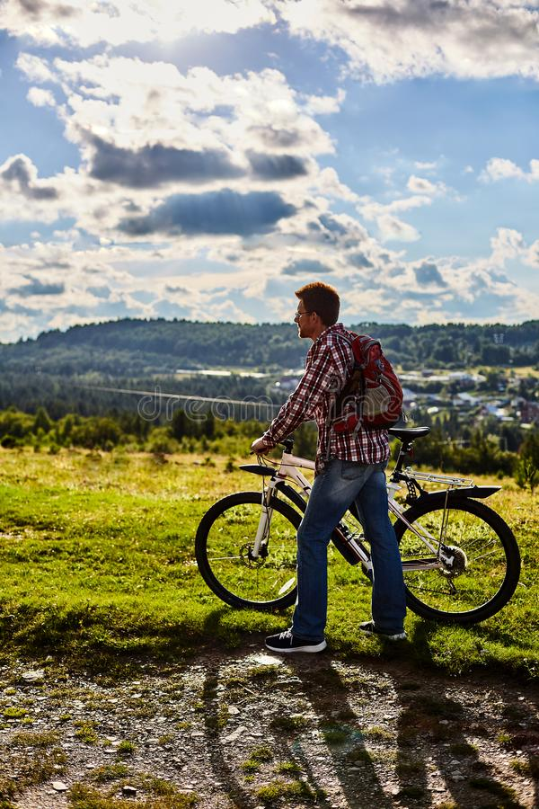 Un hombre en naturaleza con una bicicleta en el fondo de montañas y del cielo azul foto de archivo