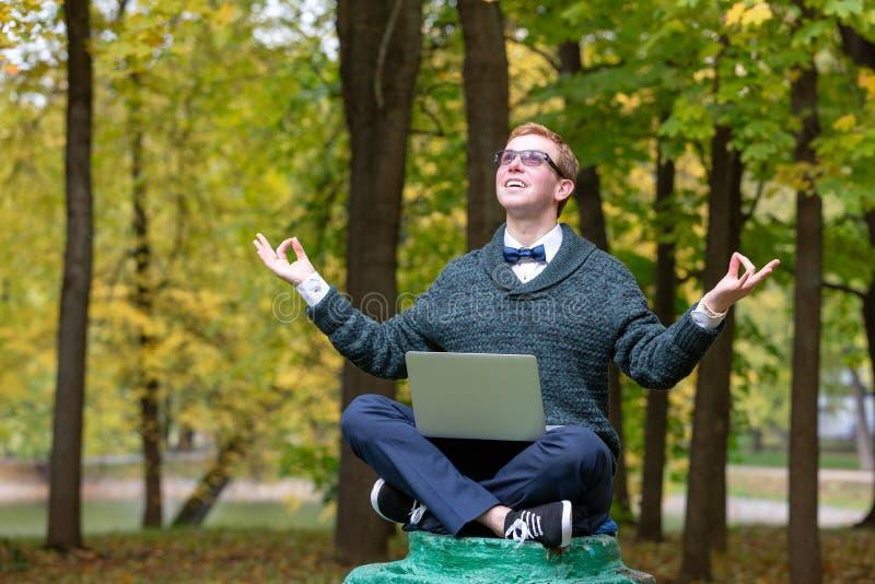 Un hombre en un pedestal que finja ser una estatua medita en la posición de loto en el parque imagen de archivo libre de regalías