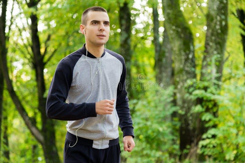 Un hombre en ropa de los deportes está corriendo alrededor foto de archivo libre de regalías