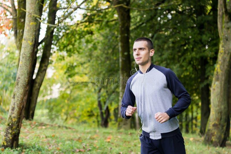 Un hombre en ropa de los deportes está corriendo alrededor foto de archivo