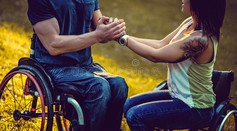 Un hombre en silla de ruedas sostiene los brazos de la hembra perjudicada fotografía de archivo libre de regalías