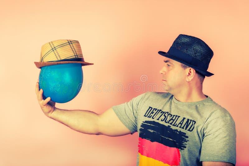 Un hombre en un sombrero de paja sostiene un globo en su mano en un sombrero, concepto de amistad con un amigo imaginado imagenes de archivo