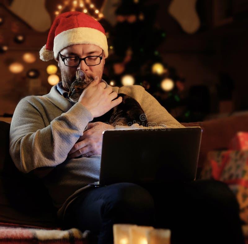 Un hombre en sombrero del Año Nuevo del ` s de Papá Noel celebra un gato y el trabajo con el ordenador portátil imagen de archivo libre de regalías