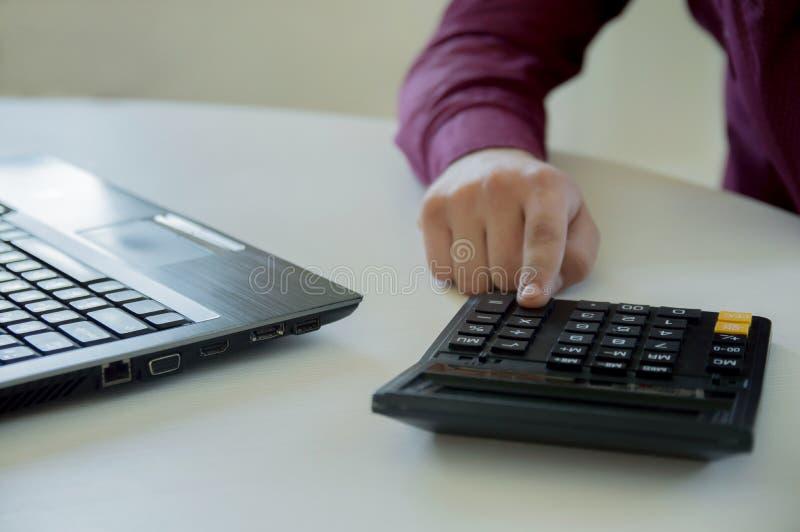 Un hombre en trabajos de una oficina detrás de un ordenador portátil y cuentas en una calculadora Mano con una calculadora Hombre imagenes de archivo