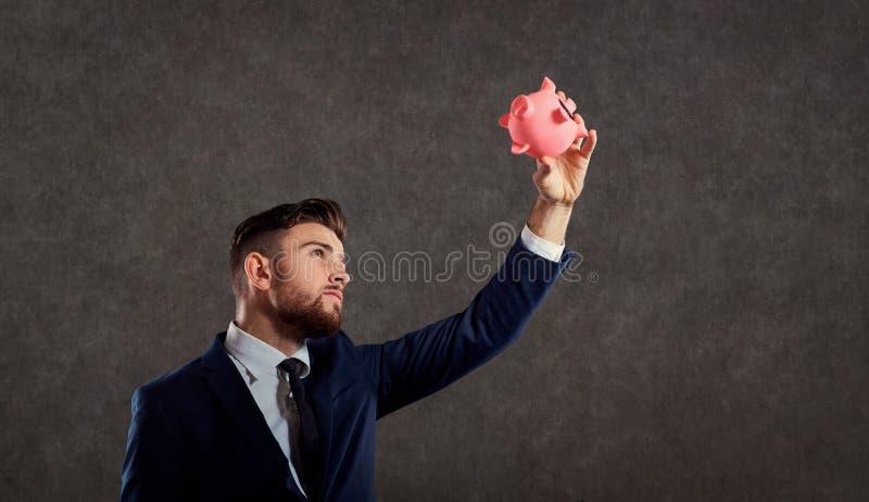 Un hombre en un traje con una hucha fotos de archivo