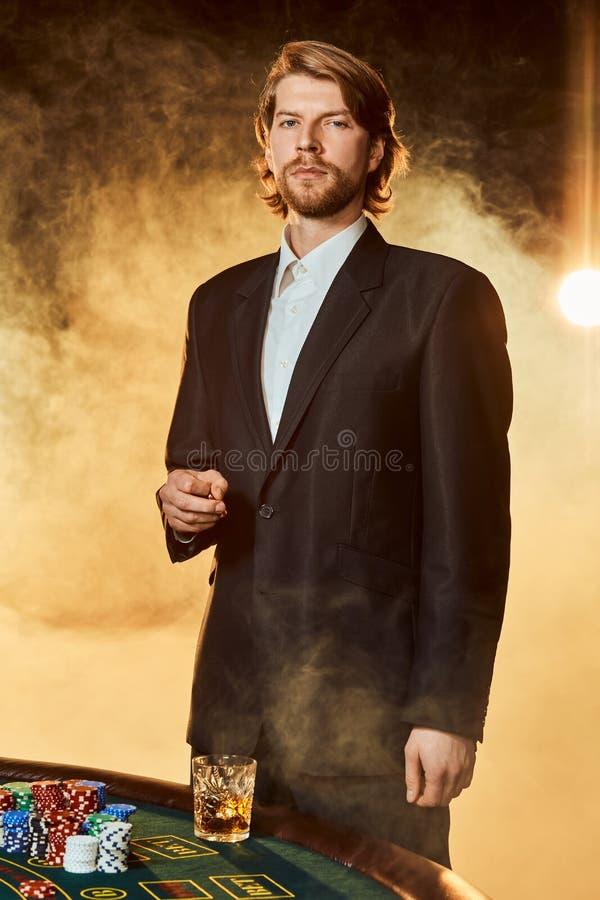 Un hombre en un traje de negocios que se coloca cerca de la mesa de juegos Jugador masculino Pasión, tarjetas, microprocesadores, foto de archivo libre de regalías