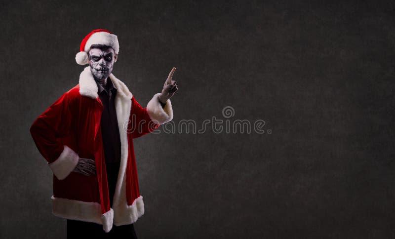 Un hombre en traje del ` s de Papá Noel con un esqueleto del maquillaje en su cara foto de archivo libre de regalías