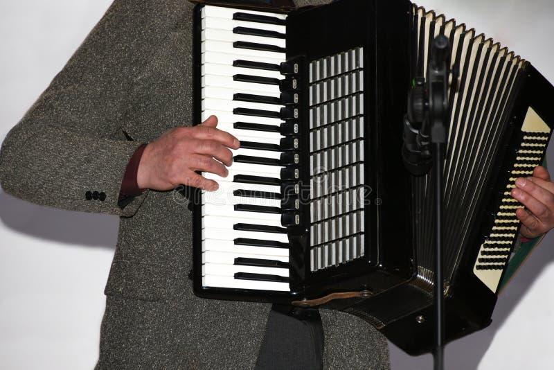 Un hombre en un traje juega el acordeón fotografía de archivo