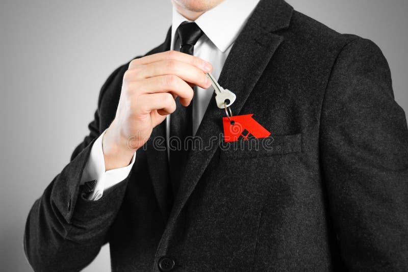 Un hombre en un traje negro lleva a cabo las llaves a la casa Rojo del llavero foto de archivo libre de regalías