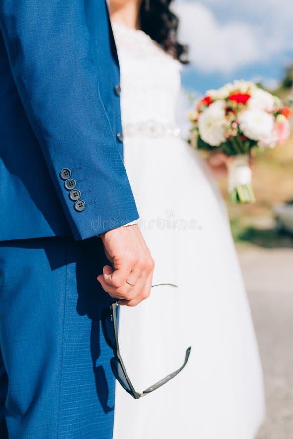 Un hombre en un traje azul está sosteniendo las gafas de sol en su mano Un weddin foto de archivo libre de regalías